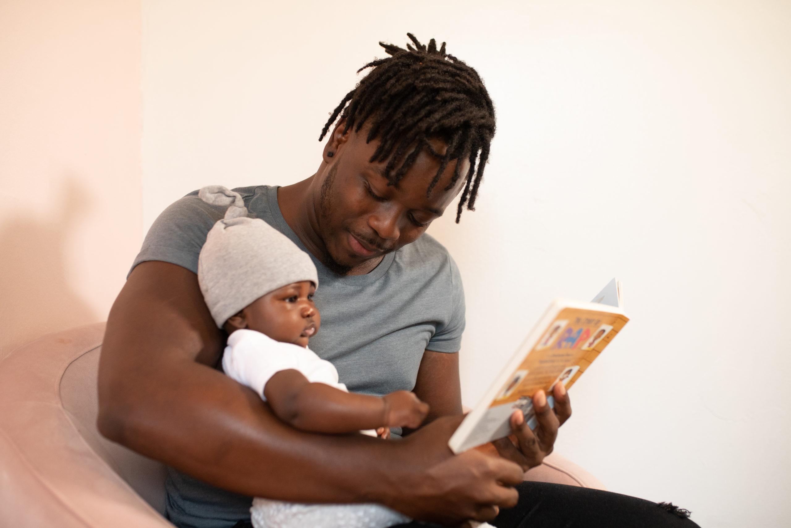 Man in gray shirt holding baby in white onesie